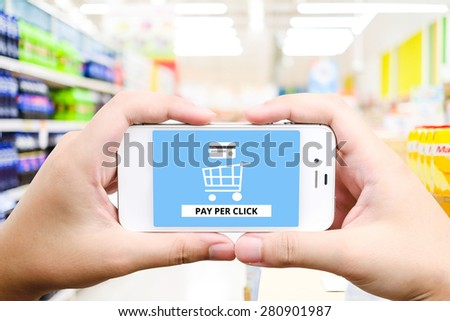 Pay per click on smart phone screen with blurred supermarket background, business, E-commerce, technology and digital marketing concept - stock photo