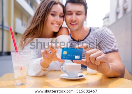 Pay the bill. Attractive young couple holding plastic credit card while siting in sidewalk cafe. - stock photo