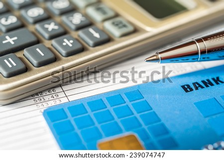 Pay the bills, bank card with a calculator and pen on the table - stock photo