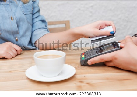 Paying for coffee. Close-up portrait of woman paying for her coffee with help of payment terminal. - stock photo