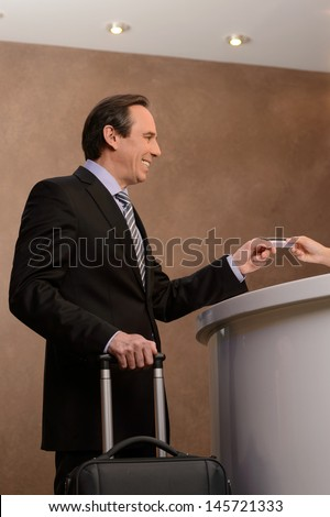 Paying for the hotel room. Cheerful mature businessman standing on the hotel reception and giving a credit card to receptionist - stock photo