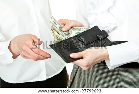 Paying money: closeup of woman's hands taking dollar banknotes out from wallet and giving them to other woman - stock photo
