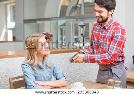 Paying price. Young handsome waiter giving payment terminal to beautiful blond-haired client. - stock photo