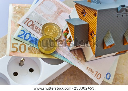 payment for electricity in model family house - energy supply and power outlet with euro money - stock photo