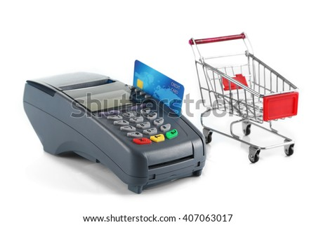 Payment terminal with inserted credit card and supermarket trolley, isolated on white - stock photo