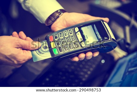 Payment with credit card - man put the credit card into a reader in vintage color tone effect - stock photo