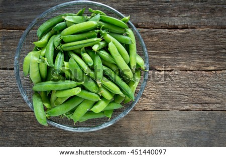 pea pods on wooden surface - stock photo