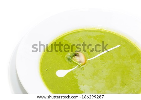 pea soup decorated with mushrooms and green on a white plate in a restaurant - stock photo