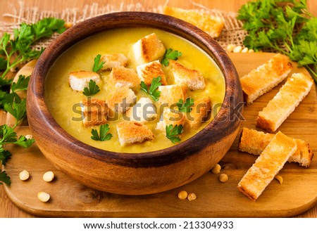 Pea soup in the wooden dish - stock photo