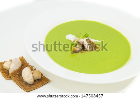 pea soup on a white dish at restaurant - stock photo