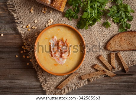 Pea soup traditional German dinner foood with greens, bacon and croutons in clay dish on vintage wooden table background. Rustic style - stock photo
