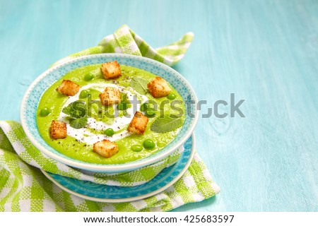 Pea soup with mint and fried bread chips - stock photo