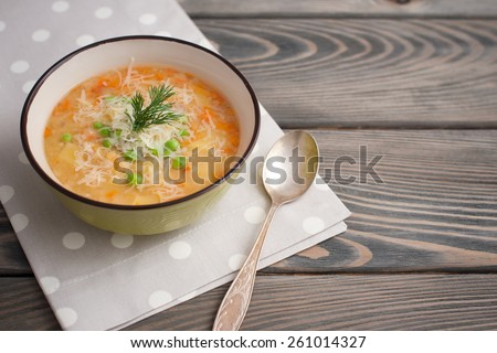 Pea soup with parmesan on wooden background. - stock photo