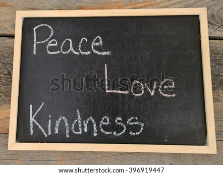 peace, love, kindness written in chalk on a chalkboard on a rustic background - stock photo