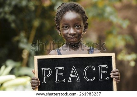 Peace On Earth - African Girl Holding Chalkboard. African girl holding a big peace symbol. - stock photo