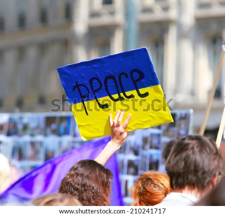 Peace sign on the ukrainian flag in protest manifestation against war in Ukraine - stock photo