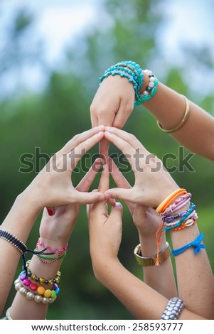 peace sign or symbol made with hands by group of youth - stock photo