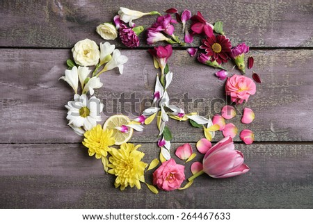 Peace symbol of beautiful flowers, on wooden table  - stock photo