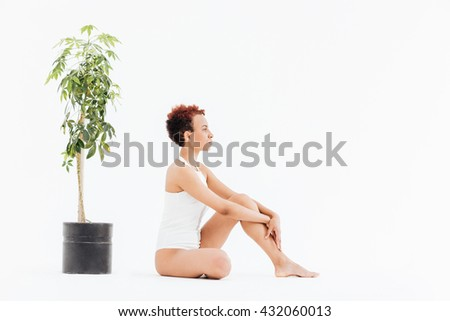 Peaceful african american young woman sitting near small tree in pot over white background - stock photo