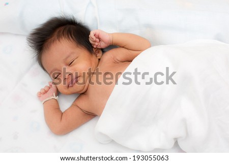Peaceful baby lying on a bed while sleeping in a bright room - stock photo
