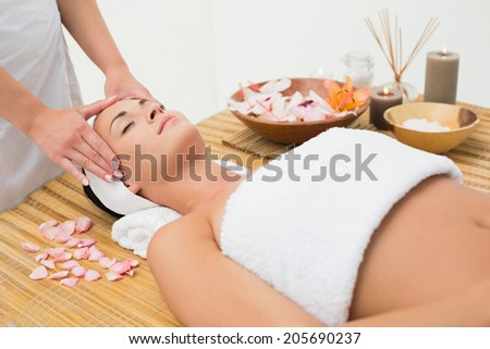 Peaceful brunette enjoying a head massage in the health spa - stock photo