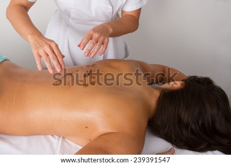 Peaceful brunette getting a chocolate scrub beauty treatment - stock photo