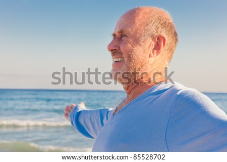 peaceful carefree older man with outstretched arms enjoying happy retirement on the coast - stock photo