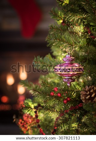 Peaceful Christmas Tree Scene with Vintage Pink Ornament, white lights, red berries and stocking and fireplace in background. Vertical warm, moody closeup and room or space for copy, text, your words - stock photo