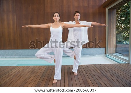 Peaceful couple in white doing yoga together in tree position in health spa - stock photo