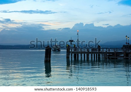 Peaceful evening on Lago di Garda in Italy, with Jetty pier in Sirmione and the last ferry boat for the day. Romantic italian summer night theme. - stock photo
