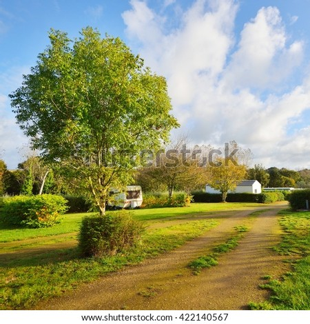 Peaceful green camping place with caravan trailer parked - stock photo