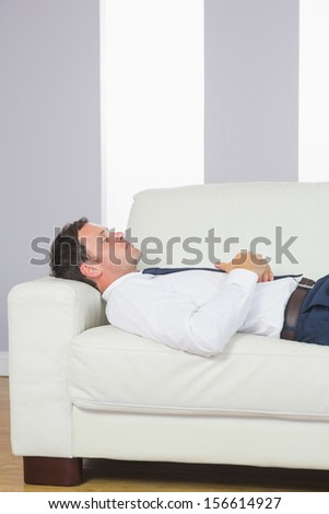Peaceful handsome businessman lying on couch after work at home - stock photo