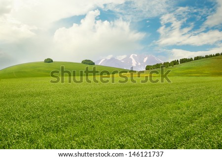 Peaceful landscape with meadow, hills, mountains and sky - stock photo