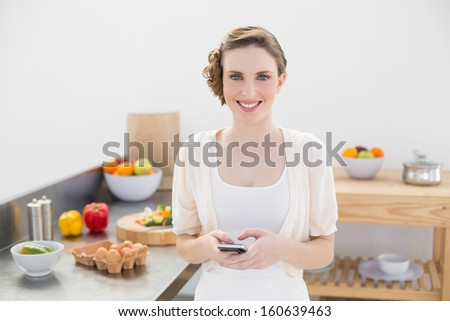 Peaceful lovely woman holding her smartphone standing in the kitchen smiling at camera - stock photo