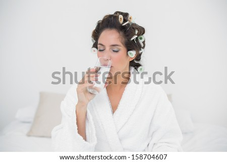 Peaceful natural brunette drinking glass of water in bedroom - stock photo