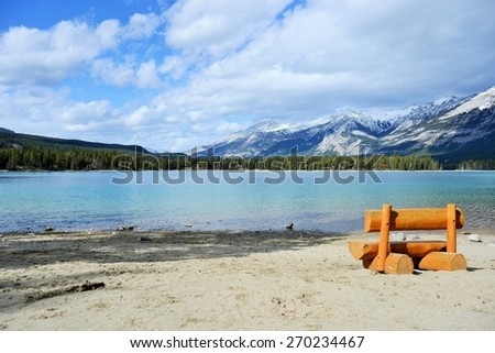 Peaceful Orange Bench with Spectacular View of Clear Lake and Rocky Mountains - stock photo
