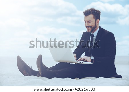 Peaceful place to work. Cheerful young man in formalwear working on laptop while sitting on sand in desert - stock photo
