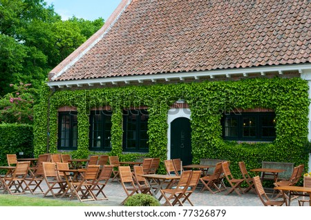 peaceful romantic outdoor restaurant by old building - stock photo
