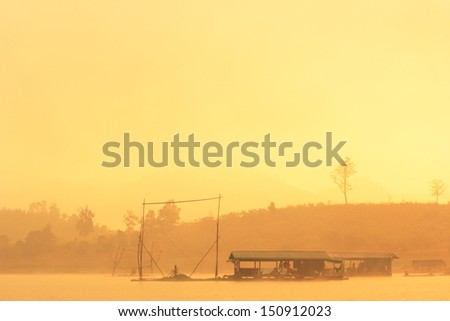 peaceful scene of lake with pier on water at morning with fog - stock photo