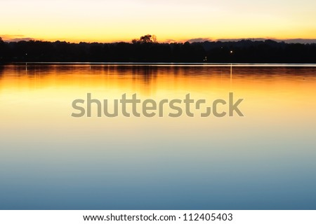 Peaceful scene with distant city lights and soft reflections on calm, still lake at sundown. Taken at Tidal Basin, Washington DC early fall. - stock photo