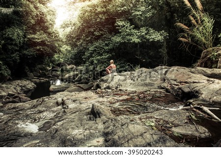 peaceful scene with meditating young woman enjoying the pristine beauty of nature in the tropical rain forest at the waterfall  during sunset. Rays of light breaking through the dense foliage - stock photo