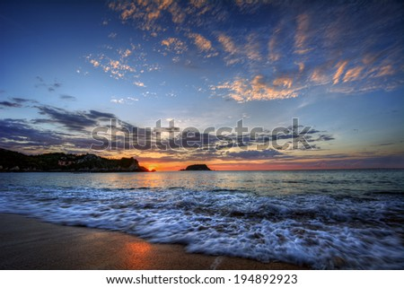 Peaceful sea bay dawn with blue skies and breaking wave and distant cliffs - stock photo