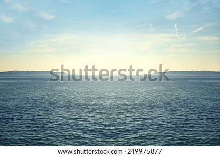 Peaceful seascape at midday with blue sky - stock photo
