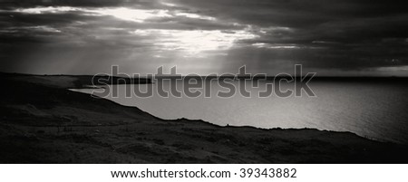 Peaceful seascape with sun rays breaking through the clouds (=fingers of god) on Isle of Skye, Scotland - stock photo