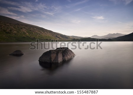 peaceful smooth water on a lake at dusk in snowdonia, north wales - stock photo