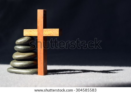 Peaceful stack of smooth stones with a simple wooden cross and shadow - stock photo