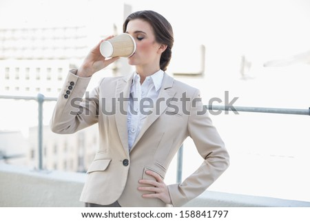 Peaceful stylish brown haired businesswoman drinking coffee outdoors - stock photo