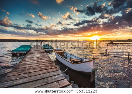 Peaceful sunset with dramatic sky and boats and a jetty - stock photo