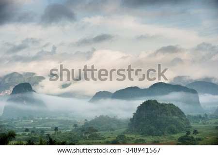 Peaceful view of Vinales valley at sunrise. Aerial View of the Vinales Valley in Cuba. Morning twilight and fog. Fog at dawn in the Valley of Vinales in Pinar del Rio, famous for tobacco plantations - stock photo