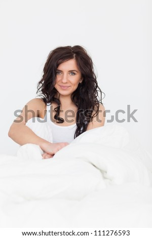 Peaceful woman sitting in her bed while waking up in her bedroom - stock photo